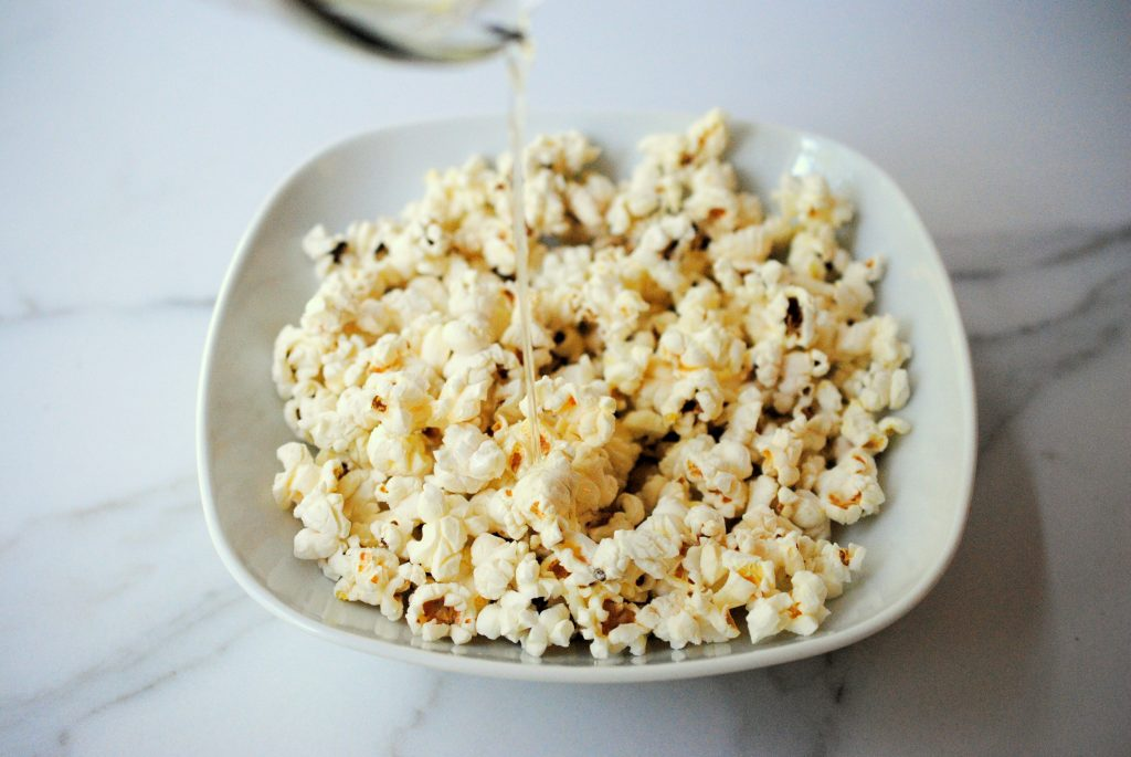Pouring vanilla coconut oil over the popcorn