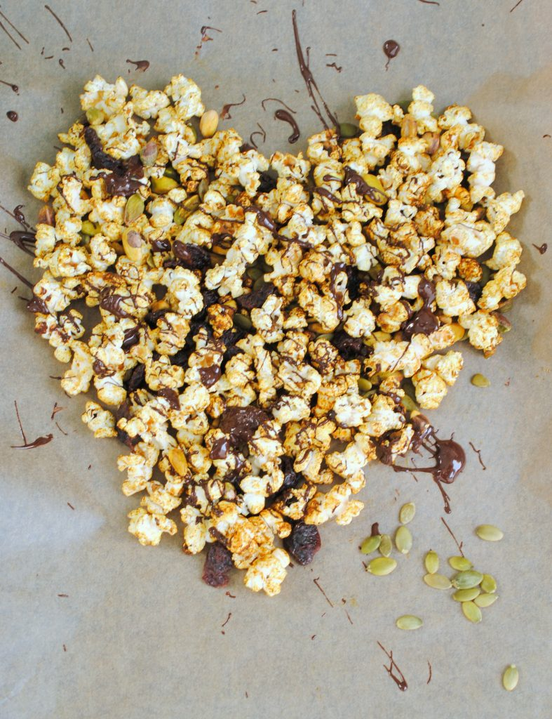 Arrange the trail mix over parchment paper (adorable heart shape not required but fun) to prepare for chocolate drizzle!