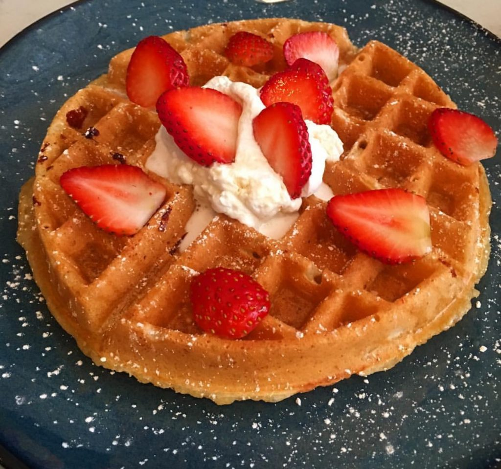 Vegan waffles topped with coconut whipped cream and strawberries... *drool*